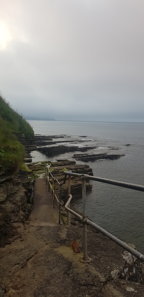 End of the steps and railings leading into the sea.