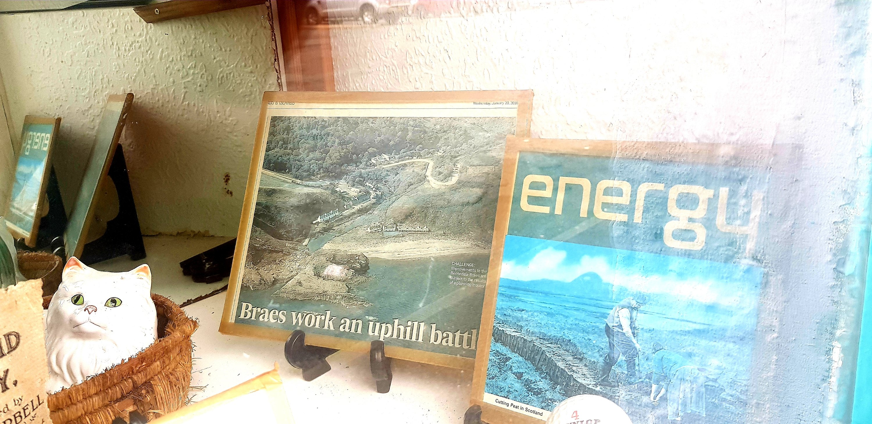 A collection of knick knacks, a news clipping about the Berridale Braes and a picture from an energy magazine.