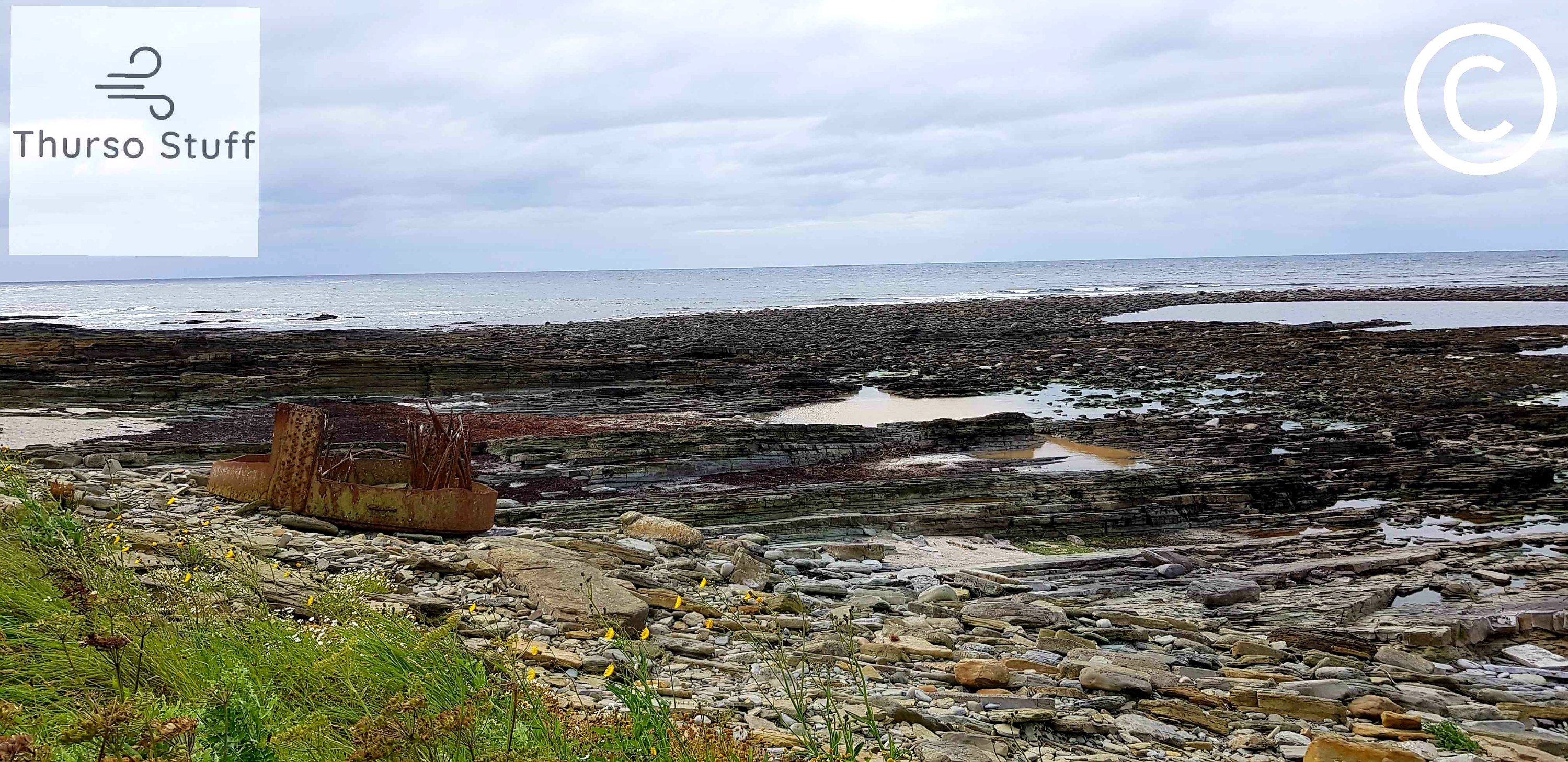 marwick bay, a rocky beach with the sea in the background